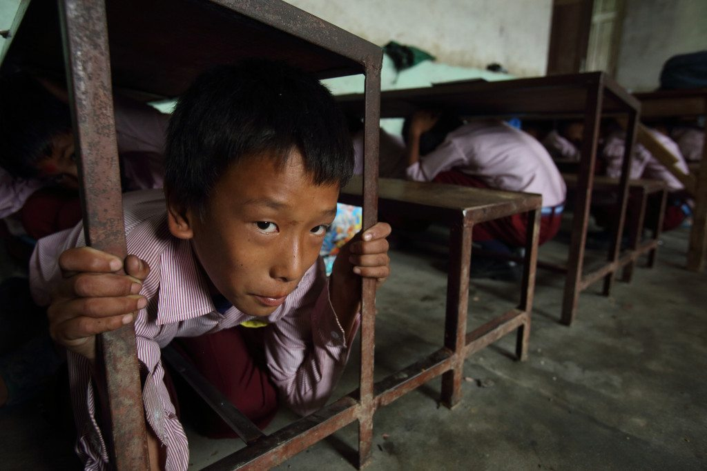 Students hide under desks during practice for aftershock. Photo Credit: DFID UK