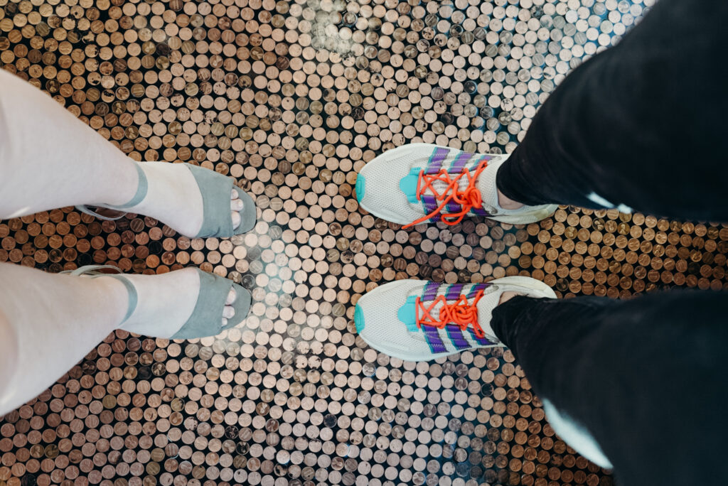 a person in heels and a person in bright colored tennis shoes stand toe to toe on a floor made of pennies