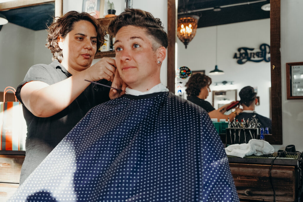 female barber using clippers on an androgynous womans hair