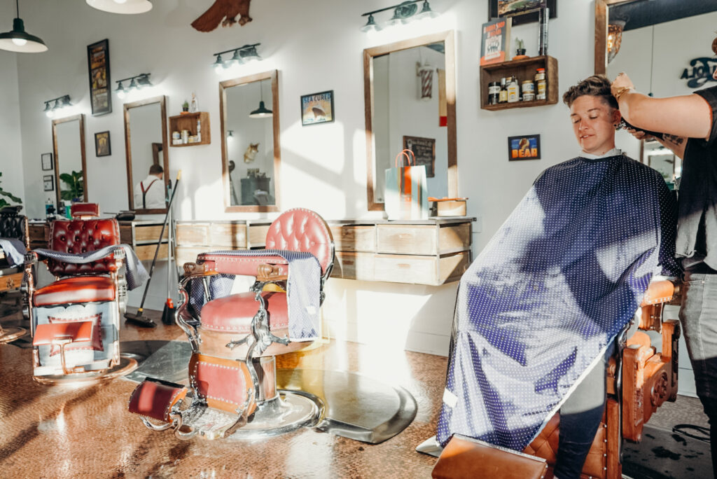 androgynous person sitting in a vintage barber chair