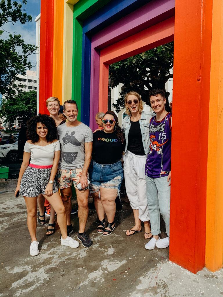 lesbians under a rainbow arch in San Juan