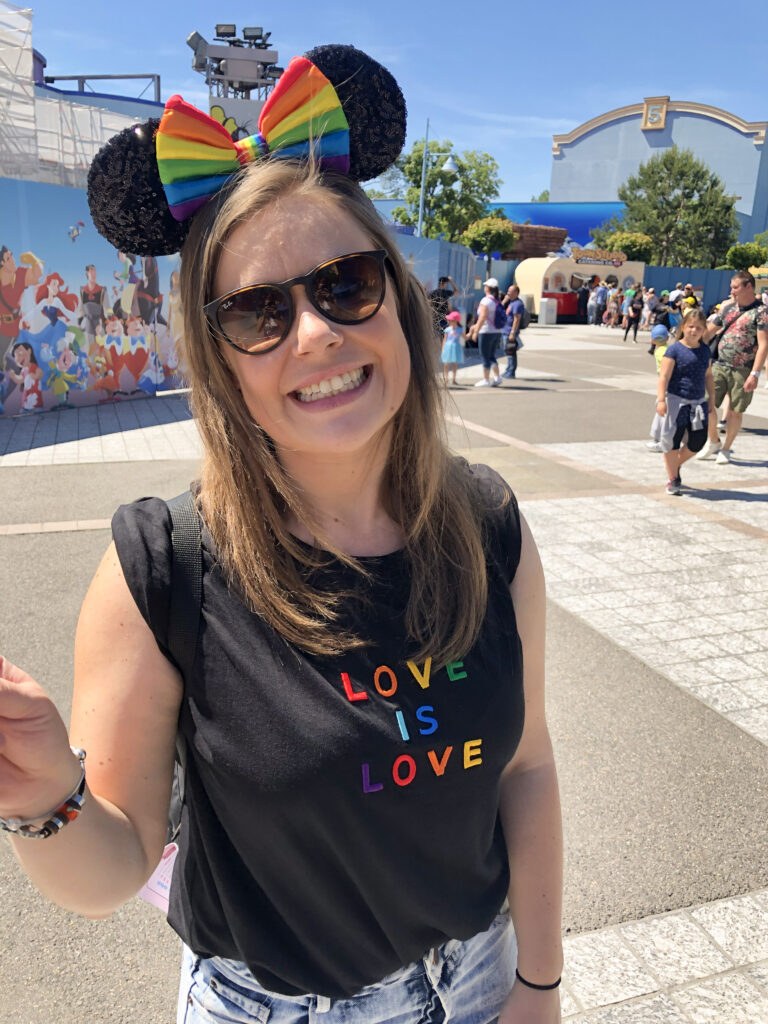 a woman wearing a black love is love shirt and rainbow Mickey ears smiles during Magical Pride