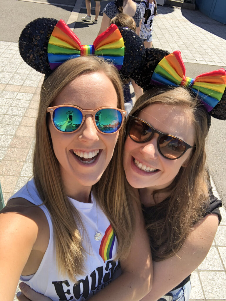 Lesbian Couple selfie wearing big smiles and rainbow Mickey ears