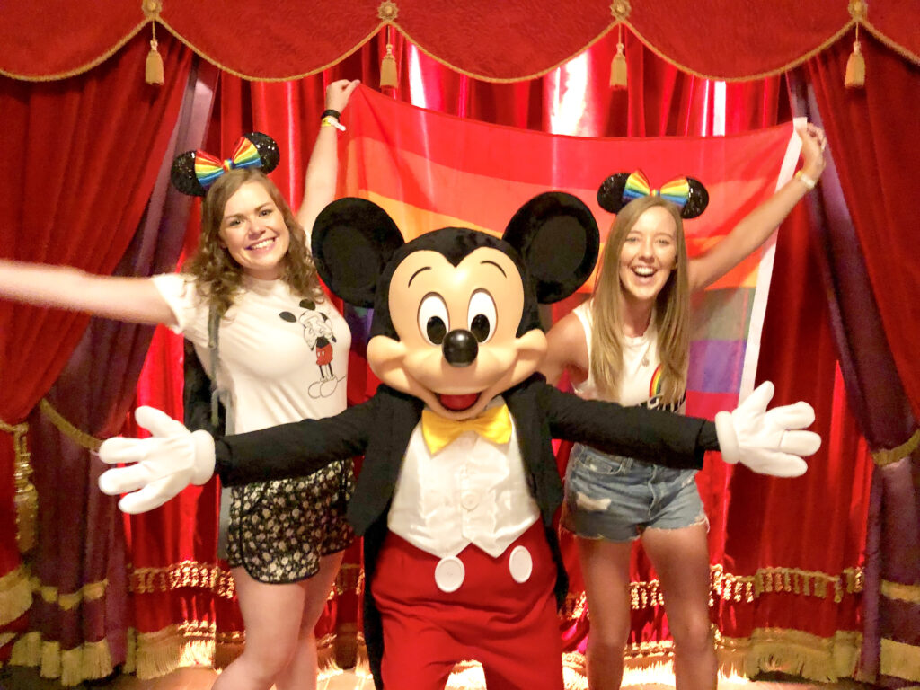 Two women wearing rainbow Mickey ears standing on either side of Mickey Mouse