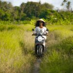 Black lesbian traveler riding a motorcycle in Thailand field